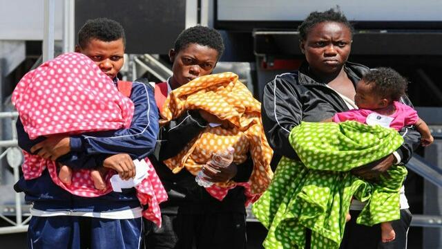 Migrants disembark from a Mediterranean rescue ship