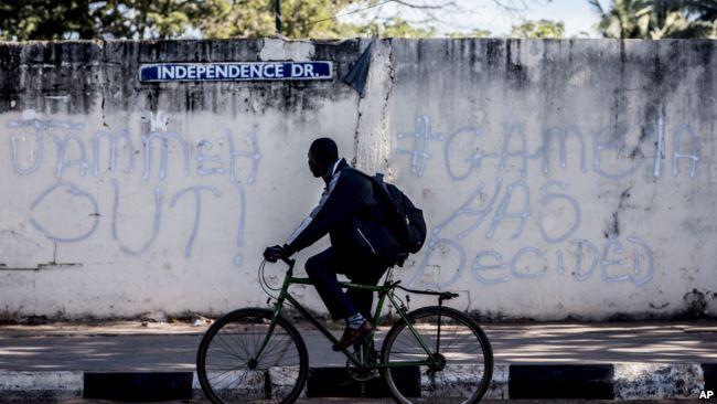 A man rides his bicycle past graffiti on a wall in Banjul, Gambia